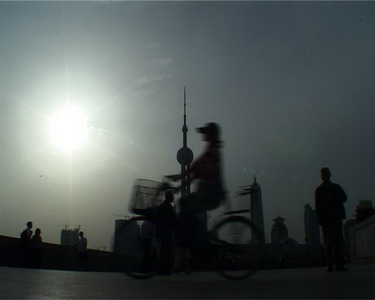 Sylvie showing to some characters how to bike in front of the camera, on the Bund